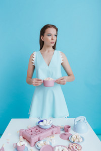 Beautiful young woman standing and holding plastic dishes with marshmallows over blue background