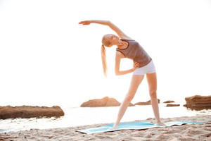 Beautiful young woman stretching hands during yoga on the beach