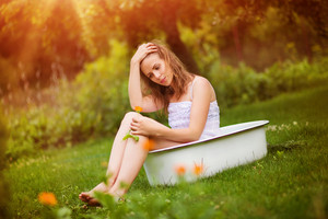 Beautiful young woman taking a herbal bath outside in a green nature.