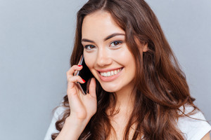Beautiful young woman talking on cell phone and looking at camera isolated on the gray background