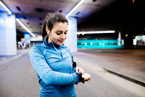 Beautiful young woman under the bridge in the town in the evening with armband, smartwatch and earphones, listening music. Using a fitness app for tracking weight loss progress, running goal or summary of her run.