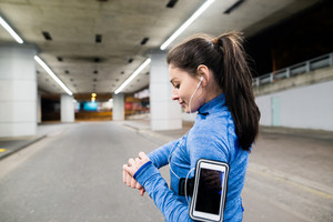 Beautiful young woman under the bridge in the town in the evening with smart phone, smartwatch and earphones, listening music. Using a fitness app for tracking weight loss progress, running goal or summary of her run.