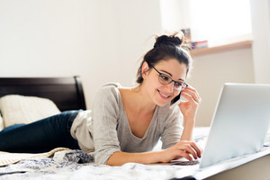 Beautiful young woman wearing eyeglasses lying on bed, working on notebook, holding a smart phone, making a phone call, home office.