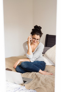 Beautiful young woman wearing eyeglasses sitting on bed, notebook next to her, holding smart phone, making a phone call, home office.