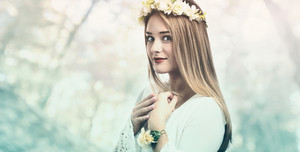 Beautiful young woman with a flower garland and a white dress