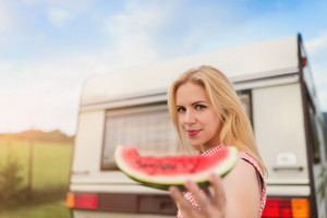 Beautiful young woman with a watermelon outside the camper van