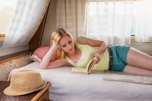 Beautiful young woman with book lying on a bed in a camper van