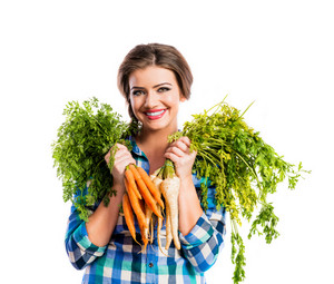 Beautiful young woman with carrots and parsley. Studio shot on white background.
