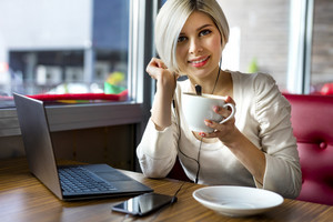 Beautiful Young Woman With Coffee Cup And Laptop In Cafe