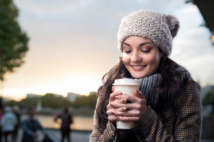 Beautiful young woman with coffee cup in the city