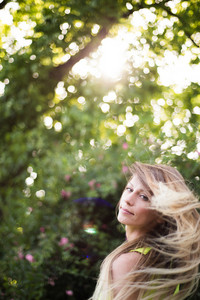 Beautiful young woman with long blowing blonde hair against green tree. Sunny summer day.
