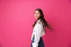 Beautiful young woman with long curly hair standing and looking at camera isolated on the pink background
