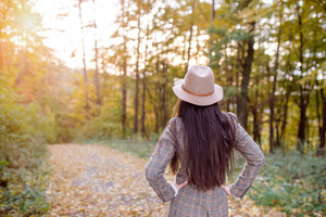 Beautiful young woman with long hair in checked coat and brown hat in autumn forest, arms on hips, rear view