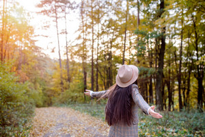 Beautiful young woman with long hair in checked coat and brown hat in autumn forest, arms stretched, rear view
