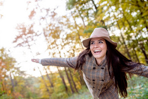 Beautiful young woman with long hair in checked coat and brown hat in autumn forest, arms stretched, smiling