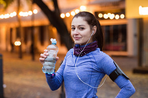 Beautiful young woman with smart phone and earphones, listening music, resting, drinking water from bottle. Running in the illuminated night town.