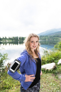 Beautiful young woman with smart phone in blue sweatshirt at the lake in green nature. Using a fitness app for tracking weight loss progress, running goal or summary of her run.