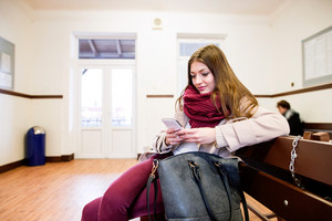 Beautiful young woman with smart phone traveling, sitting in bus waiting room.
