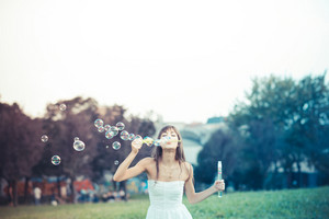 beautiful young woman with white dress blowing bubble in the city