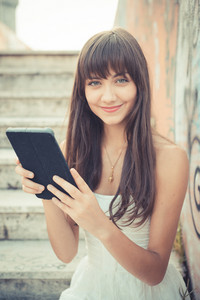beautiful young woman with white dress using tablet in the city