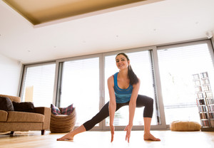 Beautiful young woman working out at home in living room, doing yoga or pilates exercise. Smiling woman stretching her leg.