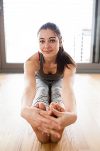 Beautiful young woman working out at home in living room, doing yoga or pilates exercise. Smiling woman stretching leg on the floor.