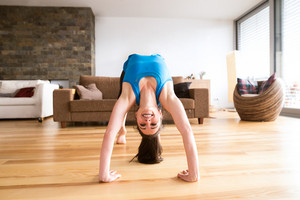 Beautiful young woman working out at home in living room, doing yoga or pilates exercise. Stretching, doing bridge pose.