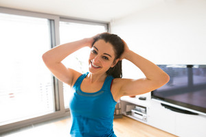 Beautiful young woman working out at home in living room, doing yoga or pilates exercise, stretching neck.