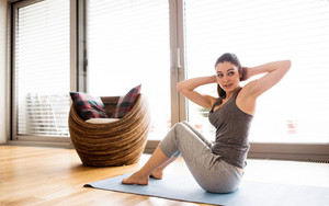 Beautiful young woman working out at home in living room, doing yoga or pilates exercise. Woman doing abdominal crunches.