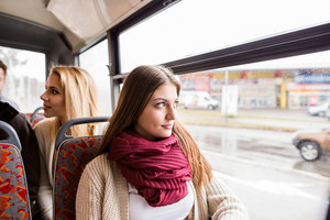 Beautiful young women traveling by bus, looking out of window, having fun in town.