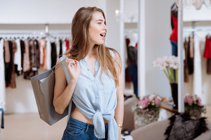Beautiul surprised young woman holding shopping bag and standing in clothing store