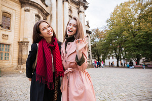 Beauty girls in coats on the street. grimace. looking at the camera