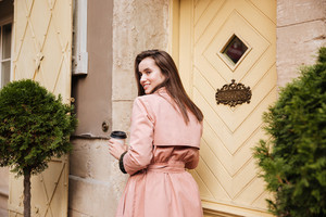 Beauty model in coat with coffee. from the back