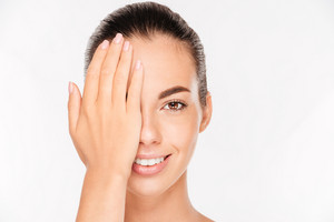 Beauty portrait of a charming woman with skin care covering face with palm isolated on a white background