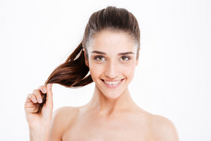 Beauty portrait of happy young woman touching her hair over white background