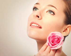 Beauty shot of a young woman with blue eyes close up holding a pink rose