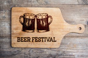 Beer festival sign with two hand drawn beer mugs on cutting board. Wooden background. Studio shot.