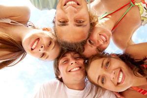 Below view of joyful teens looking at camera with smiles on vacation