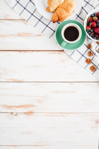 Berries, nuts, croissans and cup of coffee an wooden background