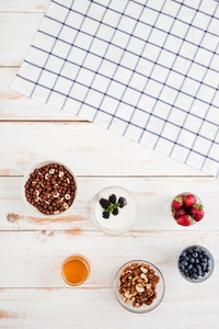 Berries, nuts, honey and plaid napkin on wooden background