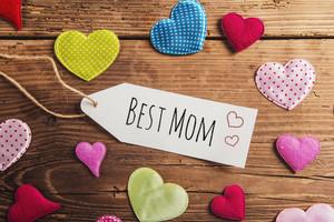 Best mom tag. Mothers day composition. Colorful fabric hearts. Studio shot on wooden background.