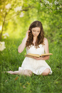 Beutiful young woman reading book in green park