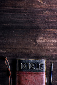 Bible, eyeglasses and pen laid on old wooden table, sign made of cookie cutters, copy space
