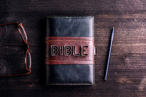 Bible, eyeglasses and pen laid on old wooden table, sign made of cookie cutters
