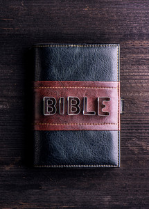 Bible in leather book cover laid on old wooden table, sign made of cookie cutters