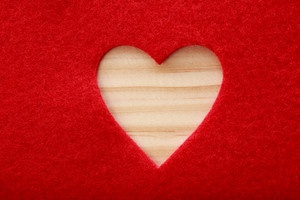 Big heart cut out of red felt with wood texture underneath