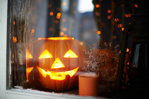 Big pumpkin with burning candle inside in a window