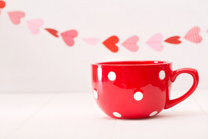 Big red coffee mug with white polka dots and hearts garland