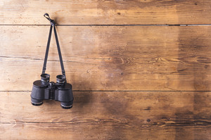 Binoculars hang on a wooden fence background