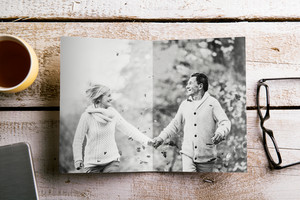 Black-and-white photo of senior couple in love in autumn nature. Eyeglasses, cup of coffee and smart phone on a table. Studio shot on white wooden background.